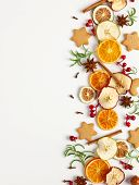 Christmas composition with cookies, dried oranges, cinnamon sticks and herbs on white background. Na poster