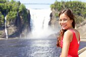 image of chute  - Chute montmorency falls quebec and woman tourist smiling happy in red summer dress looking at - JPG