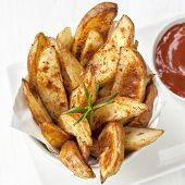 Potato wedges with rosemary and tomato ketchup.