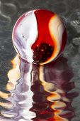 foto of dimples  - A red and white swirl marble on reflective dimpled metal - JPG