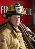 foto of firehose  - brave portrait of a firefighter standing in front of fire engine in uniform holding a fire hose - JPG