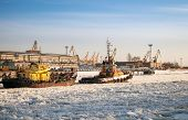 Small Tug Boat Goes With Vessel Through Icy Channel In Harbor Of St.petersburg Cargo Port