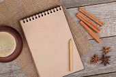 Blank notepad for copy space with coffee cup and spices on wooden table