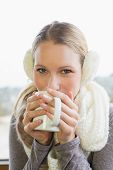 Close-up portrait of a smiling young woman wearing earmuff while drinking coffee