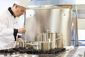Concentrated head chef stirring in pot in professional kitchen