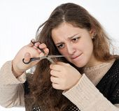 image of split ends  - woman mows split ends of hair with scissors - JPG