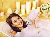 Woman relaxing at water in bubble bath.