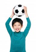 Asian little boy raise soccer ball up