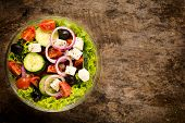 foto of cook eating  - Organic Spring salad from above on the wooden background with blank space on right side - JPG