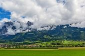 Green field, mountains covered with white clouds and villages on slopes in Germany.