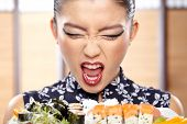 pic of sushi  - Beautiful sushi woman showing a plate of sushi - JPG