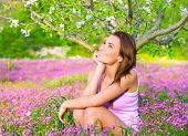 Dreamy woman spending time in blooming park, enjoying first blossom of nature, happy weekend in coun