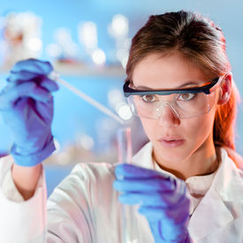 stock photo of chemistry technician  - Focused young life science professional pipetting solution into the glass cuvette - JPG