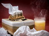 picture of tissue box  - Tissue box in knit encasement and hot flu medicine drink over dark red background - JPG