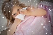 stock photo of blanket snow  - Composite image of girl suffering from cold as she lies in bed against snow falling - JPG