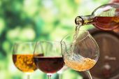 stock photo of merlot  - Red wine pouring into wine glass - JPG