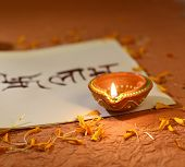 stock photo of sanskrit  - Indian traditional lamp placed on a book with Sanskrit calligraphy - JPG