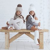 stock photo of leg warmer  - Cute little girls of 5 years old wearing knitted trendy winter clothes posing over white brick wall - JPG