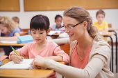 foto of pupils  - Pretty teacher helping pupil in classroom at the elementary school - JPG