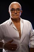 stock photo of 55-60 years old  - Portrait of old playboy in white shirt and lots of gold jewels - JPG