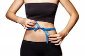 pic of outfits  - Fit and healthy young lady measuring her waist with a tape measure in centimeters and millimeters - JPG