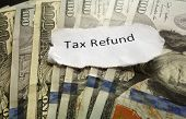 stock photo of irs  - Tax Refund paper text on assorted cash - JPG