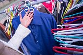 pic of stall  - Female hands choosing clothes on a market stall - JPG