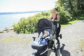 image of buggy  - A Young mother jogging with a baby buggy - JPG