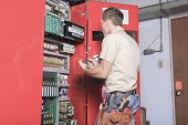 picture of adjustable-spanner  - machinist worker technicians at work adjusting lift with spanners in elevator hoistway - JPG