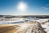 picture of slippery-roads  - winter slippery road with turns going into horizon on a bright sunny sky background - JPG