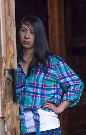 image of post-teen  - A woman wearing a casual plaid shirt stands nect to a wooden post. ** Note: Visible grain at 100%, best at smaller sizes - JPG