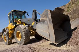 stock photo of power-shovel  - bulldozer in action in a big quarry - JPG