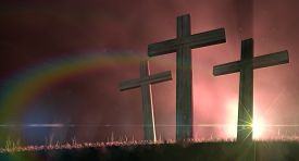 picture of crucifixion  - A concept of the crucifixion with three wooden crucifixes on a grassy hill backlit by an early morning sunrise - JPG