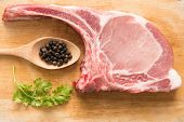 pic of pork chop  - Fresh Raw Pork Chops and pepper in spoon on wooden background - JPG