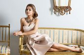 stock photo of aristocrat  - Rich woman with aristocratic style lying on antique sofa in aristocratic room and looking in camera. Wearing elegant pink dress and precious necklace.