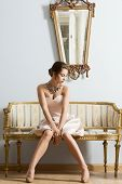 stock photo of aristocrat  - Sensual brunette woman with elegant dress and classic hair-style sitting on vintage sofa in aristocratic room. Interior luxury fashion portrait ** Note: Visible grain at 100%, best at smaller sizes - JPG