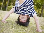 picture of upside  - little asian boy playing upside down on grass in a park - JPG