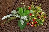 picture of bundle  - bundle of wild strawberry over wooden backgound - JPG