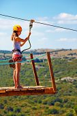 image of descending  - young woman are ready to descend on zipline in mountain extreme sport - JPG