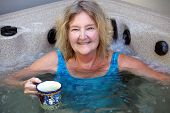 stock photo of tub  - Mature female blond beauty relaxing in her hot tub.