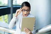picture of jaw drop  - Closeup portrait funny young woman astonished surprised wide open mouth large eyes in black glasses by what she sees on her gray silver tablet pad isolated indoors office background - JPG