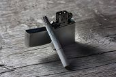 stock photo of combustion  - combustible cigarette with a lighter on the wooden table - JPG