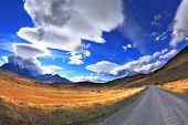 pic of snow capped mountains  - Gray dirt road in the Chile National Park  - JPG