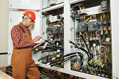 stock photo of assembly line  - adult electrician builder engineer worker with electric scheme plan in front of fuse switch board - JPG