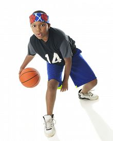 stock photo of tween  - An African American tween basketball player actively dribbling his ball - JPG