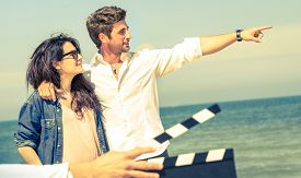 foto of slating  - Young couple in love acting for romantic film at beach  - JPG