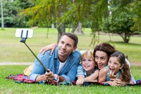 image of selfie  - Happy family in the park taking selfie on a sunny day - JPG
