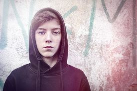 image of hoodie  - portrait of a teenage boy with black hoodie in front of a graffiti - JPG