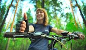 Young smiling woman on bike  with gloves. Focus on hand