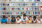 Teacher and kids lying on floor using digital tablet in library at elementary school poster